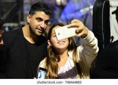 TEL AVIV, ISRAEL - November 04 2017: Israeli girl takes a selfie with the singer Moshe Peretz during a memorial rally to former prime minister of Israel Yitzhak Rabin