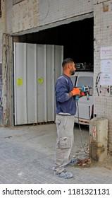 Tel Aviv, Israel - November 30, 2017: workman drills a hole in wall outdoors in Tel Aviv, Israel