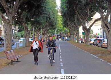 Tel Aviv, Israel - November 30, 2017: people walk by Rothschild Boulevard in Tel Aviv, Israel