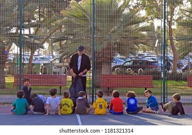 Tel Aviv, Israel - November 30, 2017: man teaches children outdoors in Tel Aviv, Israel