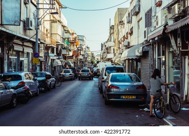 TEL AVIV, ISRAEL - OCTOBER 21, 2015. Woman with a bike on the street in Florentin district in Tel Aviv