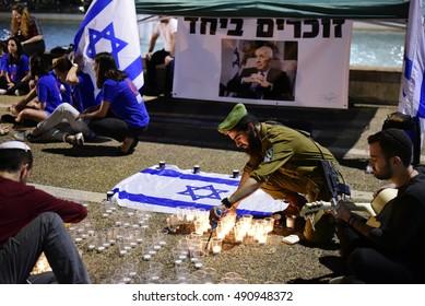 TEL AVIV, ISRAEL - SEPTEMBER 29 2016: Israeli Soldier light memory candles at Rabin square in Tel Aviv in memory of former Israeli President Shimon Peres who passed away last night at the age of 93.