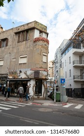 Tel Aviv, Lev Halr, Tel Aviv - Yafo, Israel - December 28, 2018: Street scene of  Old, round, corner building exterior, an unique designed, fashion dress clothes shop and two men chatting.