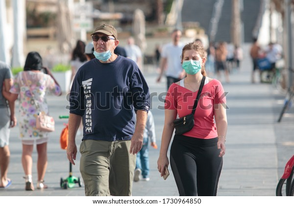 Tel Aviv – May 4th 2020: Corona epidemic lifestyle –Man with a mask tucked under his chin and woman with mask properly on, walking together at the beach promenade.