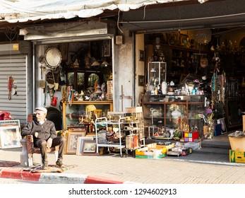 Tel Aviv, Old Jaffa, Israel - December 23, 2018: A senior seller sitting in armchair on the street in front of his antique shop in famous flea market, Old city of Jaffa, Tel Aviv