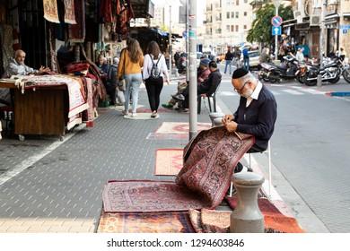 Tel Aviv, Old Jaffa, Israel - December 23, 2018: A old jew carpet seller repairing a rug on the street in front of his shop in famous flea market, Old city of Jaffa, Tel Aviv, Israel.