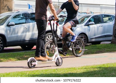 Tel Aviv Rothschild street, April 28 2018, unidentified Men riding an electric scooter and electric bicycle And talking on a cell phone