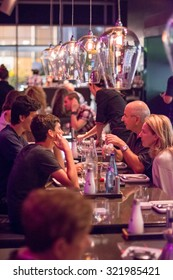 TEL AVIV, SEPT 25, 2015: People having dinner in a modern and chik open kitchen restaurant in Israel.  Part of the hip Sarona district featuring restored Templer buildings.