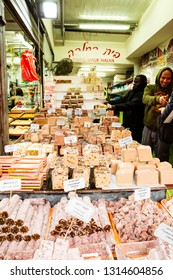 Tel Aviv, Yafo, Carmel Market, Israel - December 28, 2018: A happy smiling sellers selling home made halva (oriental sweet) at the famous Carmel Market in Tel Aviv, Israel.