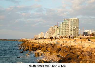 Tel Aviv - Yafo, Israel - December 23, 2018: A beautiful golden sunset scene of Tel Aviv seacoast walk, seafront rocks and the modern architecture at the horizon.