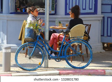 TEL AVIV, YAFO, ISRAEL - February 12, 2019. Young women are sitting on chairs, having drinks on table, retro bike with flower bouquets is parked at trendy street cafe terrace on Rothschild Boulevard.