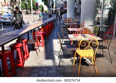 TEL AVIV,ISRAEL - FEBRUARY 18, 2017 : Street cafe open air on Allenby street. Shuk Rothschild Allenby. New Market on Rothschild Boulevard. Joyful colors of a colored wooden vacant tables and chairs