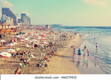 TEL AVIV,ISRAEL - JUNE 19,2015:Tel Aviv public sand beach with sun umbrellas, lounges.People swimming,relaxing and doing sport. ?mbankment,hotels in the background.Mediterranean sea.Toned colors photo