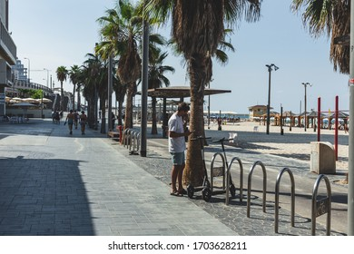 Tel Aviv/Israel-10/10/18: man is renting a Bird e-scooter via the mobile app on his smartphone on a promenade in Tel Aviv. The bird is a micromobility company operating shared electric scooters
