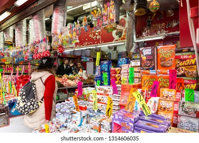 Tel Aviv-Yafo, Carmel Market, Israel - December 28, 2018:Sellers in the sweet candy shop waving and interact with the customer who chooses from great variety of candy