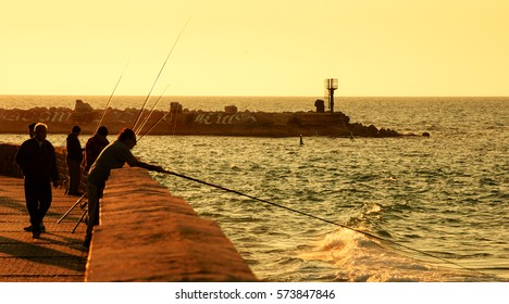 TEL AVIV-YAFO, ISRAEL - FEBRUARY 18, 2014: Silhouettes of fishermen fishing at sunset near Old Jaffa port.