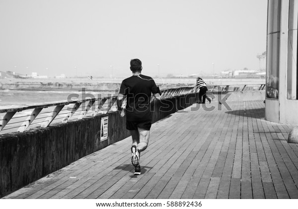 TEL AVIV-YAFO, ISRAEL - FEBRUARY 24, 2014: Mid-aged man jogging at Tel Aviv Old Port. The Port is a popular recreational and commercial area for locals and tourists.