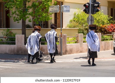 Tel Aviv-Yafo, Israel - June 9, 2018: Ultra-orthodox Hassidic Jewish men walking across Rothschild Boulevard in their traditional costumes, fur hats, black suits, tzitzits and tefilim.