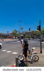 Tel Aviv-Yafo, Israel - June 9, 2018: Unidentified biker waiting to get across at Rabin Square im Tel Aviv. Biking is a popular mode of transportation in tel Aviv as well as other cities of Israel.