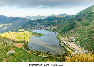 telaga cebong lake dieng with cloudy sky and surrounded by green farm field