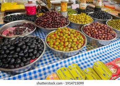 TEL-AVIV, ISRAEL - FEBRUARY 26, 2018 : black and green fermented olives in deep stainless steel basin for sale in Carmel market, Israel