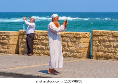 TEL-AVIV, ISRAEL - JULY 13, 2018 Muslim Old Bearded Man With Traditional Arabic clothes For Prayer To God - White Dishdasha(kandura) Making Selfie or Taking picture in Jaffa Port Tel Aviv.