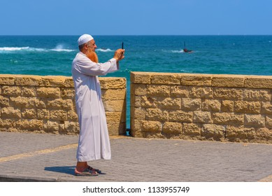 TEL-AVIV, ISRAEL - JULY 13, 2018 Muslim Senior Bearded Man With Traditional Arabic clothes For Prayer To God, Fashion Arab traditional Wear White Dishdasha(kandura) Making Selfie or using smartphone.