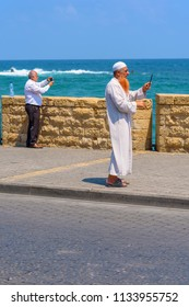 TEL-AVIV, ISRAEL - JULY 13, 2018 Muslim Elderly Bearded Man With Traditional Arabic clothes For Prayer To God-Fashion Arab traditional Wear White Dishdasha(kandura) Making Selfie or Taking photo.
