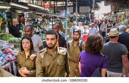 TEL-AVIV, ISRAEL - MAY 08, 2018: Israeli soldiers walk at Carmel Market, popular marketplace in Tel-Aviv. Israel