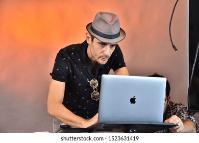 Tel-Aviv/ Israel - September 9 2019: two young men, photographers, one in a hat, bent over a Macintosh computer on an orange photophone
