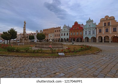 Telc, Czech Republic- AUGUST 25, 2018: Wide angle cloudy morning landscape of main square of Telc or Teltsch with Plague Column, fountain and renaissance colorful houses. A UNESCO World Heritage Site.