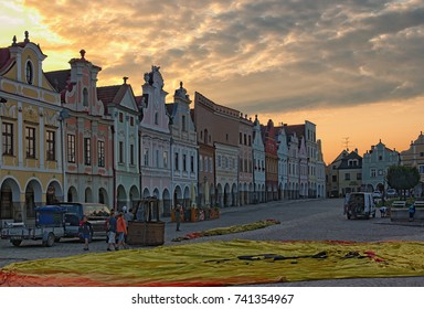 TELC, THE CZECH REPUBLIC-AUGUST 26, 2017: Preparation of a hot air balloon for flight in the main square of the city Telc. The balloon is unfolding for further air filling. Sky with sunrise.