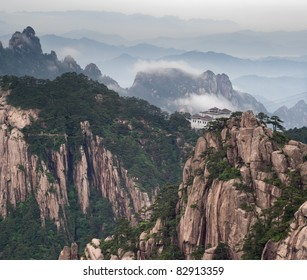 Tele image of Huangshan mountain and Chinese style house at cloudy weather, sunset. Aerial view at Yellow Mountain. China, Asia