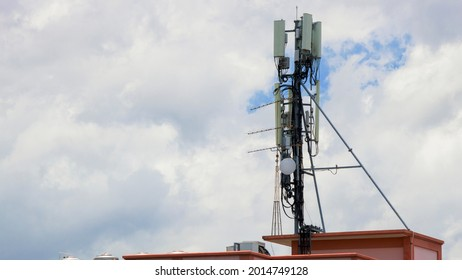 Telecom, Single Telecom mast or Telecommunication mast on the roof of the building, TV antennas wireless technology with clouds sky background, Show telecom tower infrastructure