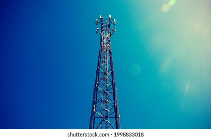 Telecom, Single Telecom mast or Telecommunication mast TV antennas wireless technology with blue sky background, Show tower infrastructure. Vintage concept with light flare