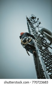 Telecom Worker Climbing Antenna Tower with Tools and Harness