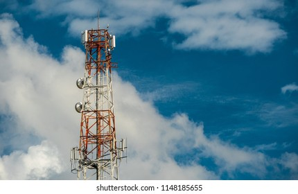 Telecommunication antenna on the top of the telecommunications service provider's building with clouds and  blue sky background in technology concept