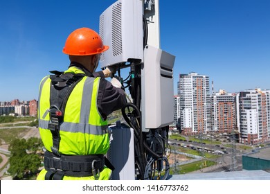 Telecommunication engineer in helmet and uniform installs telecomunication equipment in his hand and antennas of GSM DCS UMTS LTE bands, outdoor radio units, optic fibers, power cables are installed
