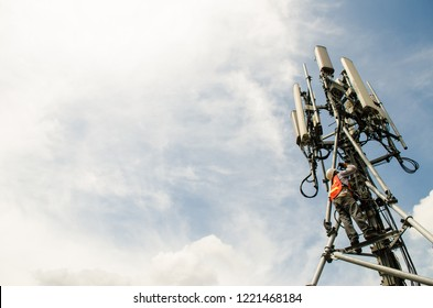 Telecommunication engineer working on high tower,Risk work of high work,Technician working with safety equipment on tower,Sky background.Technician take picture while working on tower.