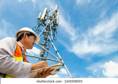 Telecommunication engineer writing on notepad at tower site.Technician record data of maintenance to checklist.
