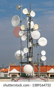 Telecommunication mast with microwave link on top roof at blue  background.
