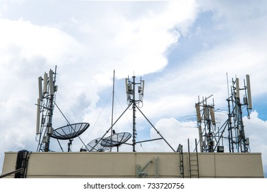 Telecommunication mobile antenna and satellite dish on roof building with blue sky. communication network technology concept.