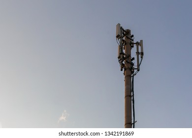 telecommunication pole with antennas and wires against the blue sky, copy space for text. Development of communication system in urban area