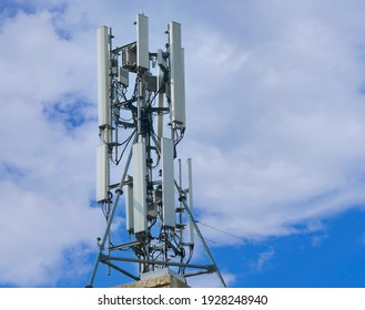 Telecommunication tower of 4G and 5G cellular. Macro Base Station. 5G radio network telecommunication equipment with radio modules and smart antennas mounted on a metal on cloulds sky background.