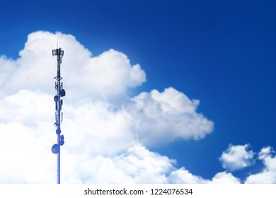 Telecommunication tower antenna at clouds sky background
