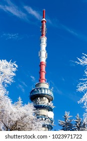 Telecommunication tower behind blue sky.