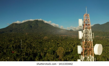 Telecommunication tower, communication antenna against mountains and rainforest, aerial view. Repeaters on a metal tower. Camiguin, Philippines