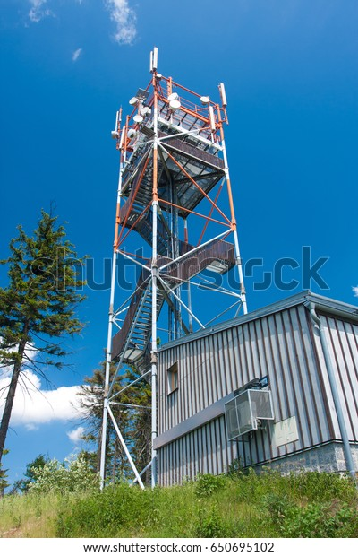 Telecommunication tower with lookout and blue sky