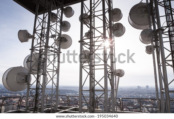 Telecommunication tower with many satellite dishes in the city