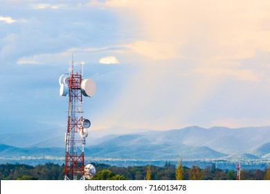 telecommunication tower with mountain range background with warm sunset light casting on clouds, good background for wireless technology or telecommunication concept with room for text or copy space